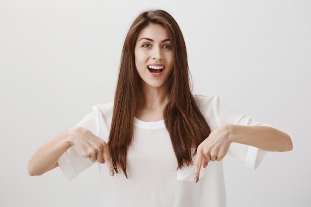Piękna dziewczyna wskazując palcami w dół, aby pokazać ogłoszenie, uśmiechając się szczęśliwy