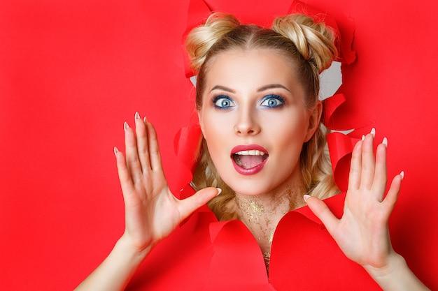 Piękna dziewczyna wspina się z dziury w czerwonym papierze