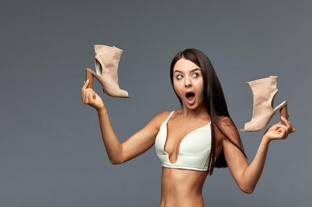 Piękna dziewczyna wybiera buty na szarym tle trudność w wyborze, co na wieczorną randkę problemy kobiet