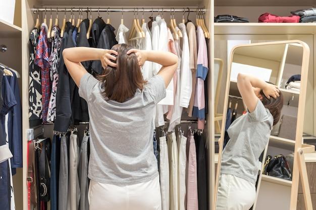 Piękna dziewczyna wybiera ubrania w swojej garderobie