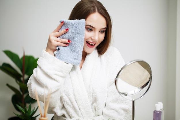 Piękna dziewczyna wyciera twarz ręcznikiem w domu przed lustrem