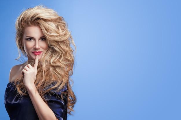 Piękna dziewczyna z bardzo dużymi luksusowymi długimi falującymi włosami w dżinsowych ubraniach na niebieskim tle.