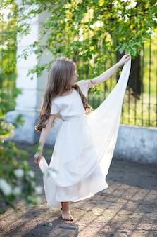 Piękna dziewczyna z blond długimi włosami w białej delikatnej jedwabnej sukni tańczy balet boso w parku z pięknym światłem