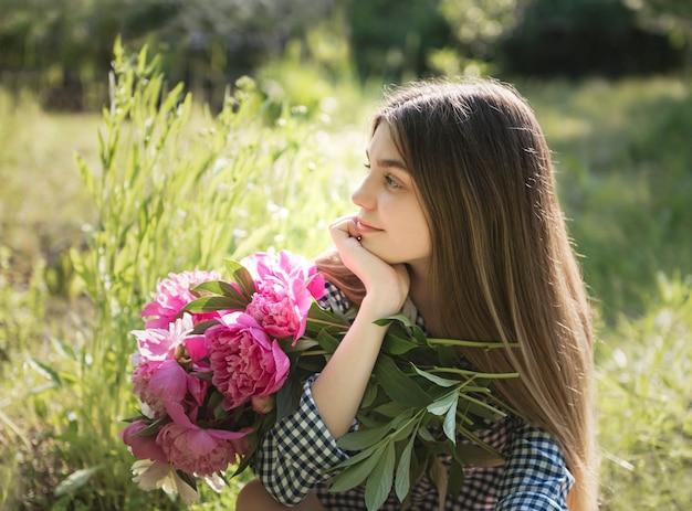 Piękna dziewczyna z bukietem piwonii