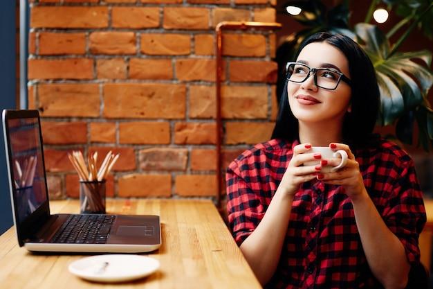 Piękna dziewczyna z czarnymi włosami w okularach siedzi w kawiarni z laptopem i filiżanką kawy, niezależna koncepcja, portret, na sobie czerwoną koszulę.