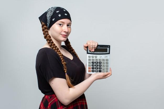 Piękna dziewczyna z czerwoną spódnicą chustka i czarny t-shirt z kalkulatorem na szarym