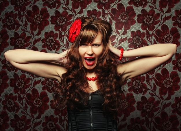 Piękna dziewczyna z czerwonym kwiatem we włosach