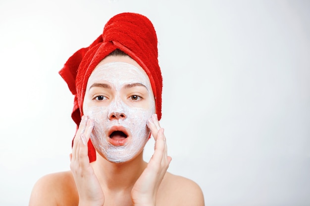 Piękna dziewczyna z czerwonym ręcznikiem na głowie nakłada peeling na twarz dużego portretu na białym