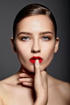 Piękna dziewczyna z czerwonymi ustami i paznokciami