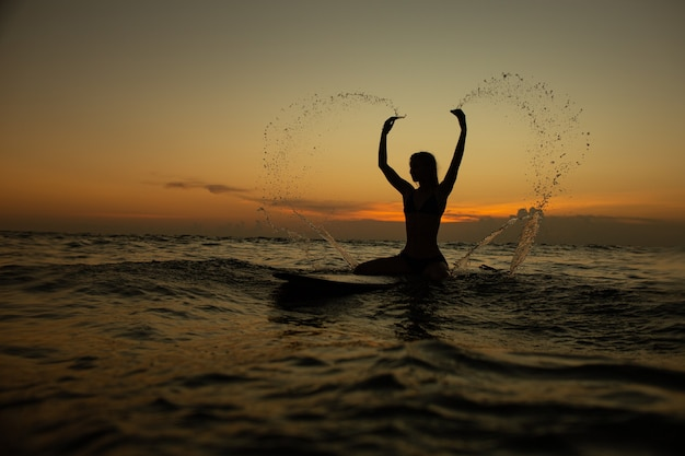 Piękna dziewczyna z deską surfingową o zachodzie słońca