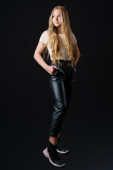 Piękna dziewczyna z długimi blond włosami w białej koszulce i czarnych skórzanych spodniach pozuje do kamery na czarnym tle