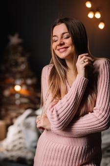 Piękna dziewczyna z długimi blond włosami w długim swetrze z zamkniętymi oczami w oczekiwaniu na święta