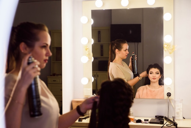 Piękna dziewczyna z długimi włosami, fryzjer tka francuski warkocz w salonie piękności. profesjonalna pielęgnacja włosów i tworzenie fryzur