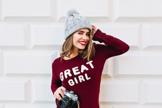 Piękna dziewczyna z długimi włosami i czerwonymi ustami w swetrze marsala na szarej ścianie. nosi dzianinową czapkę, trzyma kamerę w rękach i uśmiecha się.