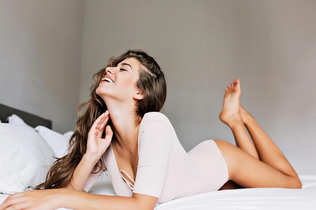 Piękna dziewczyna z długimi włosami na łóżku w nowoczesnym mieszkaniu. dotyka szyi, uśmiecha się i ma zamknięte oczy.