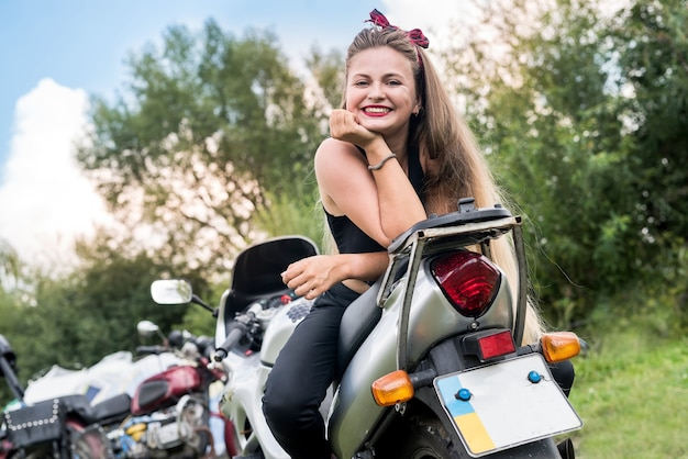 Piękna dziewczyna z długimi włosami pozowanie na motocyklu