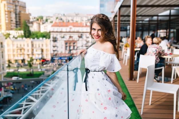 Piękna dziewczyna z długimi włosami pozuje do kamery na tarasie w kawiarni. nosi białą sukienkę z odkrytymi ramionami i czerwoną szminką.