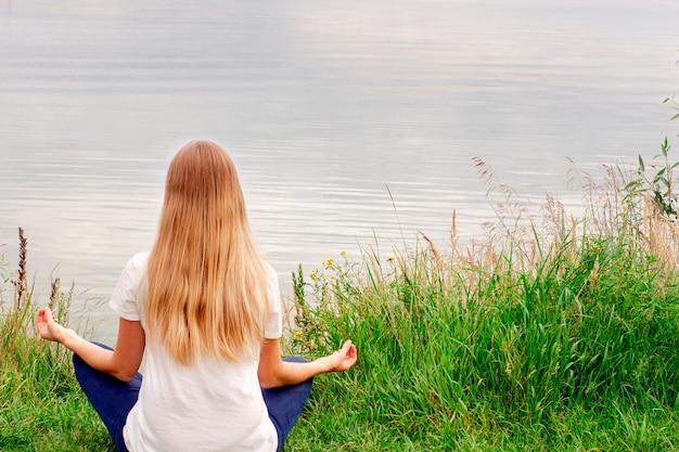 Piękna dziewczyna z długimi włosami siedzi na brzegu. widok z tyłu. zachód słońca. cisza i spokój. joga nad jeziorem
