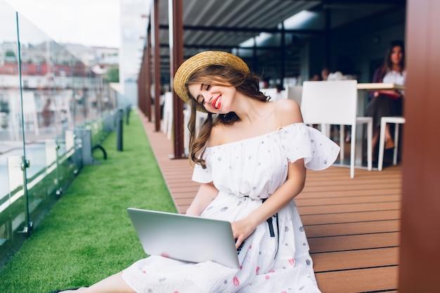 Piękna dziewczyna z długimi włosami siedzi na podłodze na tarasie. nosi białą sukienkę z odkrytymi ramionami, czerwoną szminką i kapelusz. pisze na laptopie na kolanach.