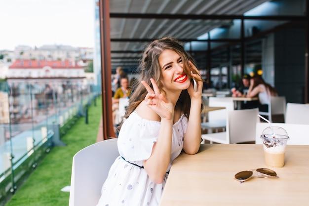 Piękna dziewczyna z długimi włosami siedzi przy stole na tarasie w kawiarni. nosi białą sukienkę z odkrytymi ramionami i czerwoną szminką. ona mówi przez telefon i uśmiecha się do kamery.