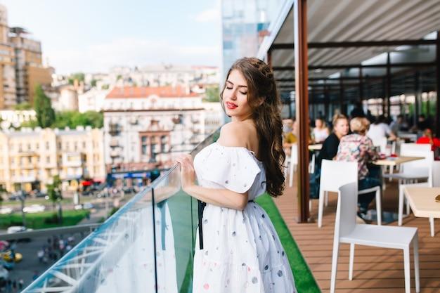 Piękna dziewczyna z długimi włosami stoi na tarasie w kawiarni. nosi białą sukienkę z odkrytymi ramionami i czerwoną szminką. ma lekki uśmiech i spogląda w dół.