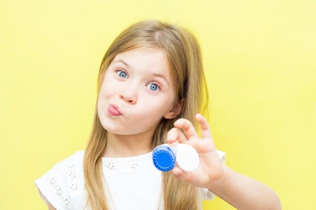 Piękna dziewczyna z długimi włosami trzyma w dłoni pojemnik z soczewkami. pojęcie problemów ze wzrokiem u dzieci. żółte tło.