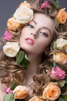 Piękna dziewczyna z dużą ilością kwiatów we włosach i jasnym różowym makijażu.