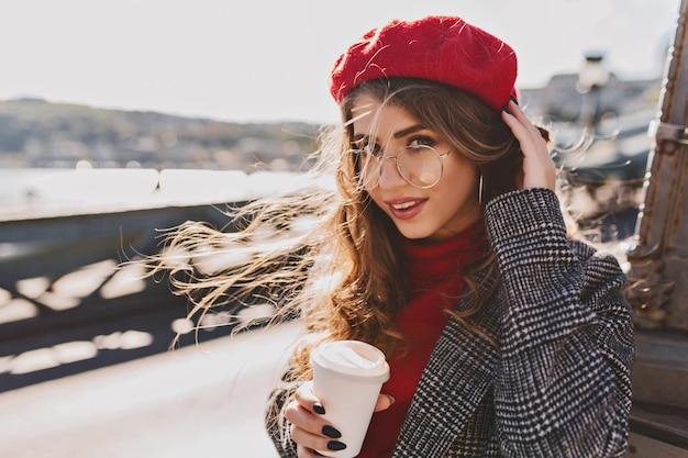 Piękna dziewczyna z dużymi niebieskimi oczami pozuje na ulicy w zimny wietrzny dzień z filiżanką kawy