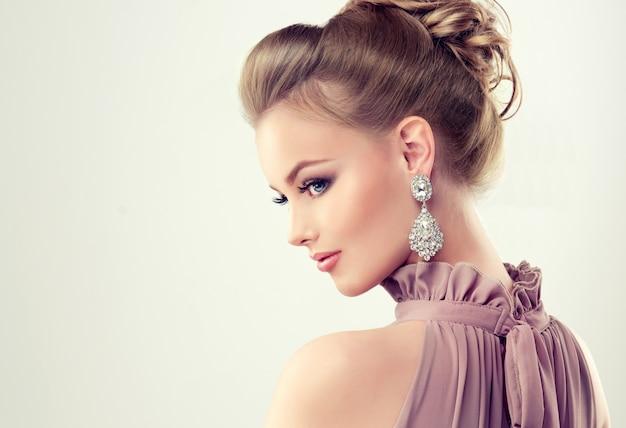 Piękna dziewczyna z elegancką fryzurą i dużymi kolczykami biżuterii