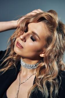 Piękna dziewczyna z falującymi blond włosami z luksusową błyszczącą ozdobą na szyi