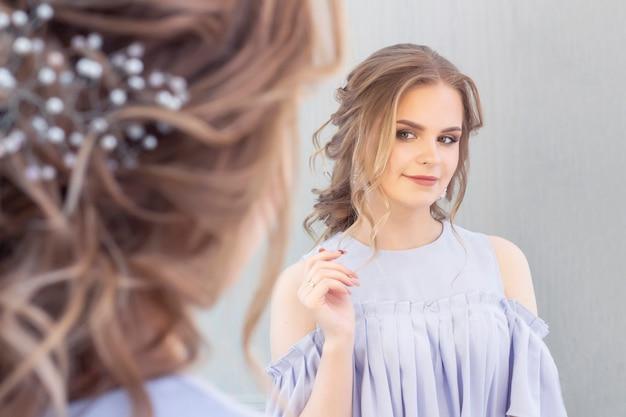 Piękna dziewczyna z fryzurą ślubną patrzy na siebie w lustrze, portret młodej dziewczyny. piękny makijaż. salon piękności