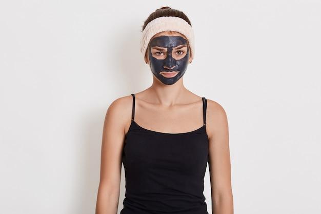 Piękna dziewczyna z glinianą maską na twarzy stojąca z zdenerwowanym wyrazem twarzy ze smutkiem, ubrana w czarną koszulkę i opaskę do włosów.