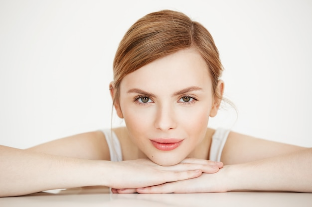 Piękna dziewczyna z idealnie czystą skórą uśmiechnięty siedzący przy stole. beauty spa i kosmetologia.