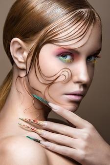 Piękna dziewczyna z jasny makijaż moda, kreatywna fryzura, długie paznokcie.