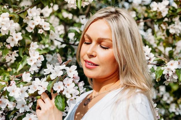 Piękna dziewczyna z jasnymi włosami, okularami, w pobliżu kwitnących drzew, jabłoni, wiosna, gałęzie, kwiat, moda, styl, europejska