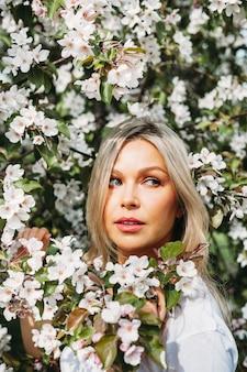 Piękna dziewczyna z jasnymi włosami, okulary, w pobliżu kwitnących drzew, jabłoń, wiosna, gałęzie, kwiat, moda, styl, europejski, czerwony
