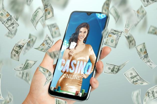Piękna dziewczyna z kartami do gry w ręku na ekranie smartfona i spadającymi dolarami. kasyno online, hazard, zakłady, ruletka. ulotka, plakat, szablon reklamy.