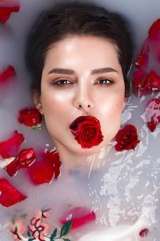 Piękna dziewczyna z klasycznym makijażem i czerwonymi ustami w łazience z kwiatami. piękna twarz. zdjęcie zrobione w studio