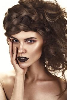 Piękna dziewczyna z kreatywną fryzurą, idealną skórą i ciemnym makijażem. piękno twarzy.