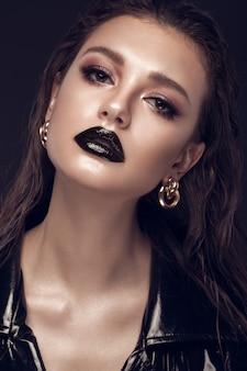Piękna dziewczyna z kreatywnym makijażem, czarną sukienką i złotymi dodatkami. piękna twarz.