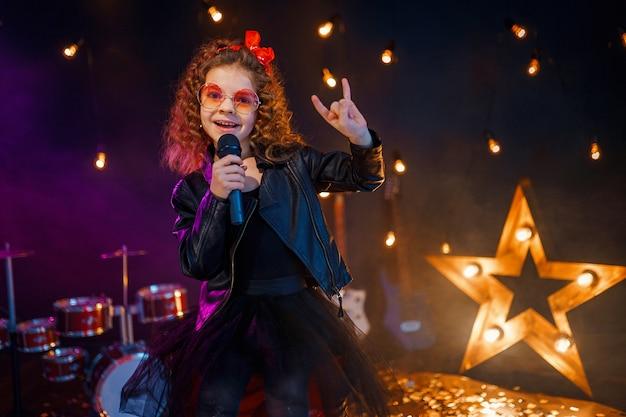 Piękna dziewczyna z kręconymi włosami w skórzanej kurtce i czerwonych okularach przeciwsłonecznych śpiewa w mikrofonie bezprzewodowym do karaoke w studio nagrań