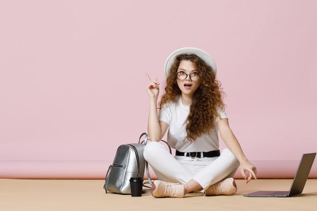 Piękna dziewczyna z kręconymi włosami w zwykłych ubraniach i okularach za pomocą laptopa