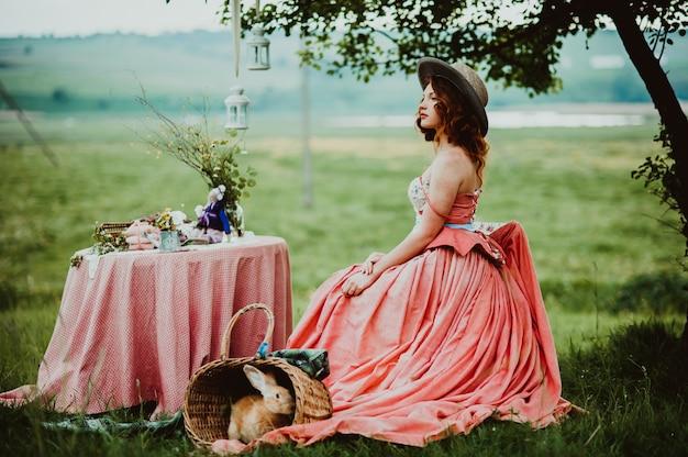 Piękna dziewczyna z królikiem na zewnątrz w letni dzień