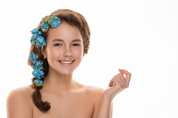 Piękna dziewczyna z kwiatami we włosach, idealna skóra.