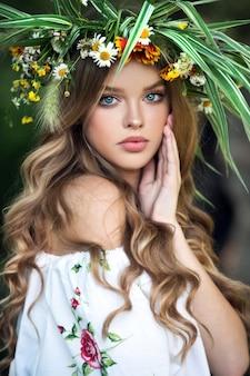 Piękna dziewczyna z kwiatu wiankiem na łące przy gospodarstwem rolnym. połowa lata. dzień ziemi.