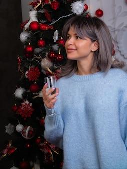 Piękna dziewczyna z lampką szampana spotyka nowy rok i boże narodzenie na choince