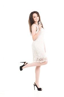 Piękna dziewczyna z lampką szampana w białej sukni. uśmiecha się do kamery. uroczystość. nowy rok. boże narodzenie