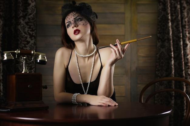 Piękna dziewczyna z lat 30. pali papierosa przy stole