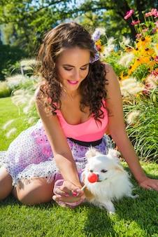 Piękna dziewczyna z małym psim chihuahua w parku