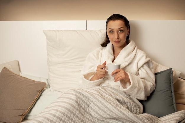 Piękna dziewczyna z mokrych włosów relaksujący siedzący w łóżku picia herbaty w szlafroku